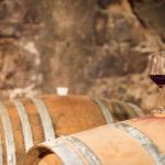 Barriquefass im Keller mit Rotweinglas